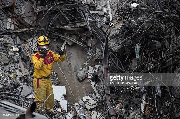 A rescue worker gestures while using a walkietalkie on what was the top of the WeiKuan complex which collapsed in the 64 magnitude earthquake in the...