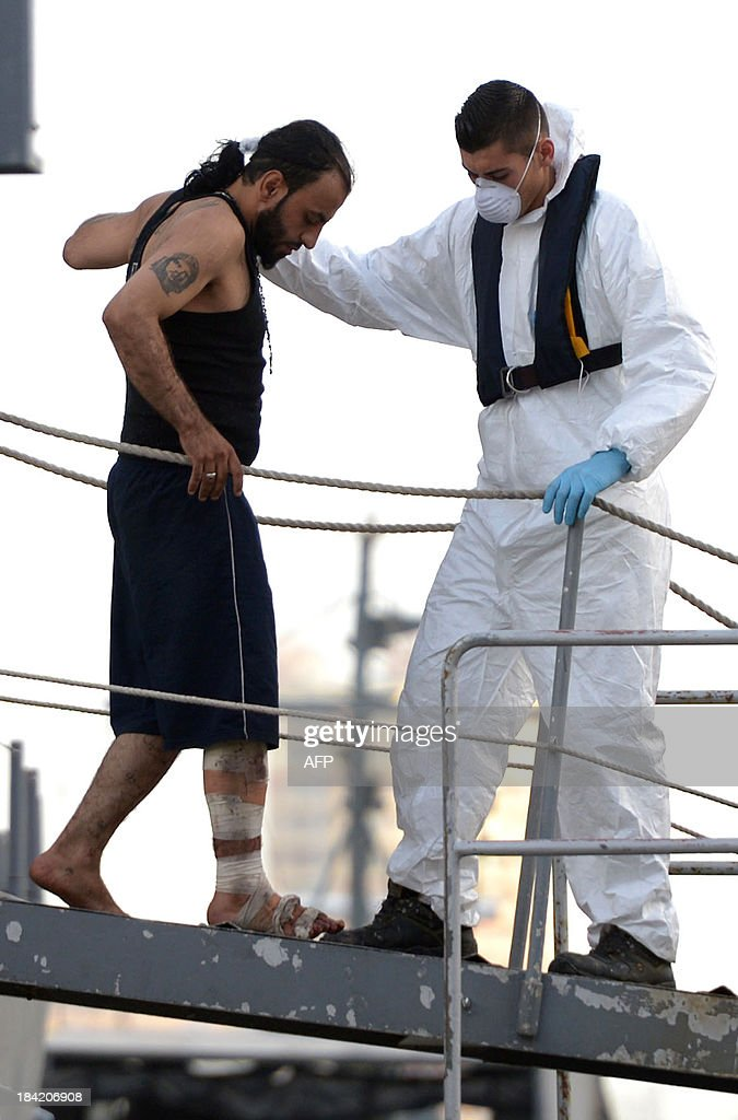 A rescue worker helps an injured migrant disembark from a patrol boat of the Armed forces of Malta at Hay Wharf in Valletta on October 12, 2013, a day after a boat carrying migrants sank. More than 140 survivors, plucked from the sea after their overloaded boat sank in the latest deadly migrant tragedy to hit the Mediterranean, arrived in Malta. The sinking killed more than 30, most of them women and children, when the boat packed with people desperate to reach European shores went down off Malta near the Italian island of Lampedusa, according to officials.