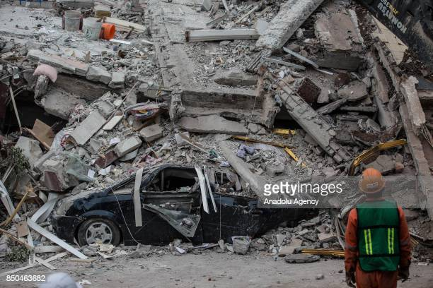 A rescue worker inspects a car under the debris of a building after a powerful magnitude 71 earthquake that hit Mexico City Mexico on September 21...