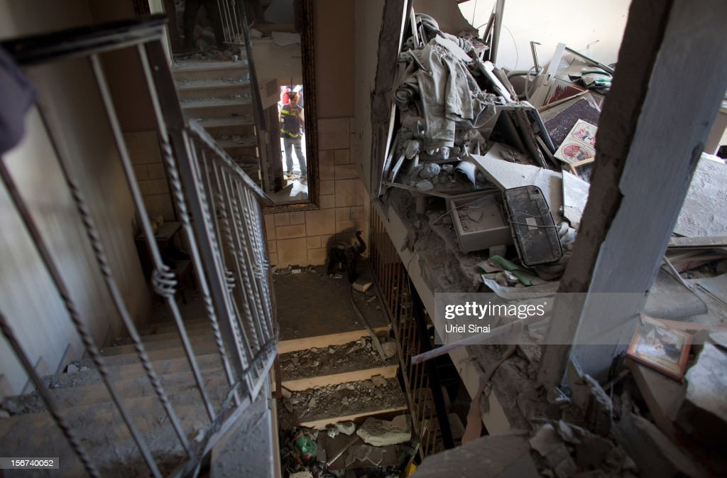 A rescue worker inspects a house after it was hit by a rocket fired from the Gaza Strip on November 20, 2012 in Beersheba, Israel. Hamas militants and Israel are continuing talks aimed at a ceasefire as the death toll in Gaza reaches over 100 with three Israelis also having been killed by rockets fired by Palestinian militants.