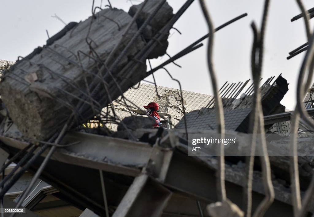 A rescue worker is pictured amongst the rubble as search operations continue at the Wei-kuan apartment complex on the second day of rescue operations following a 6.4 magnitude earthquake in southern Taiwan's city of Tainan on February 7, 2016. Rescuers searched through the night hoping to free residents trapped in buildings toppled by the deadly earthquake in Taiwan, as survivors recalled being plucked to safety from their ruined homes. AFP PHOTO / Sam Yeh / AFP / SAM YEH