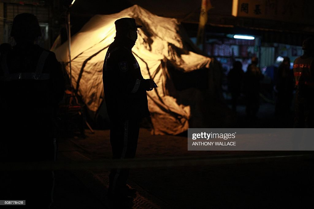 A rescue worker is silhouetted in front of a makeshift tent used to house supplies and victims before they are taken to hospital at the site of a collapsed building in the southern Taiwanese city of Tainan early on February 7, 2016 following a strong 6.4-magnitude earthquake. More than 250 people have been rescued from the Wei-kuan apartment complex in the southern city of Tainan since the quake hit at 4:00 am Saturday, killing 14 people and toppling four blocks of around 100 homes in total. WALLACE