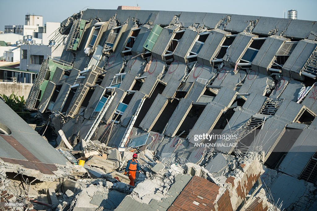 A rescue worker (C) looks for survivors as he walks on the rubble of a building which collapsed in the 6.4 magnitude earthquake, in the southern Taiwanese city of Tainan on February 8, 2016. Rescuers raced on February 7 to free around 120 people buried under the rubble of an apartment complex felled by an earthquake in southern Taiwan that left 34 confirmed dead, as an investigation began into the collapse. AFP PHOTO / ANTHONY WALLACE / AFP / ANTHONY WALLACE