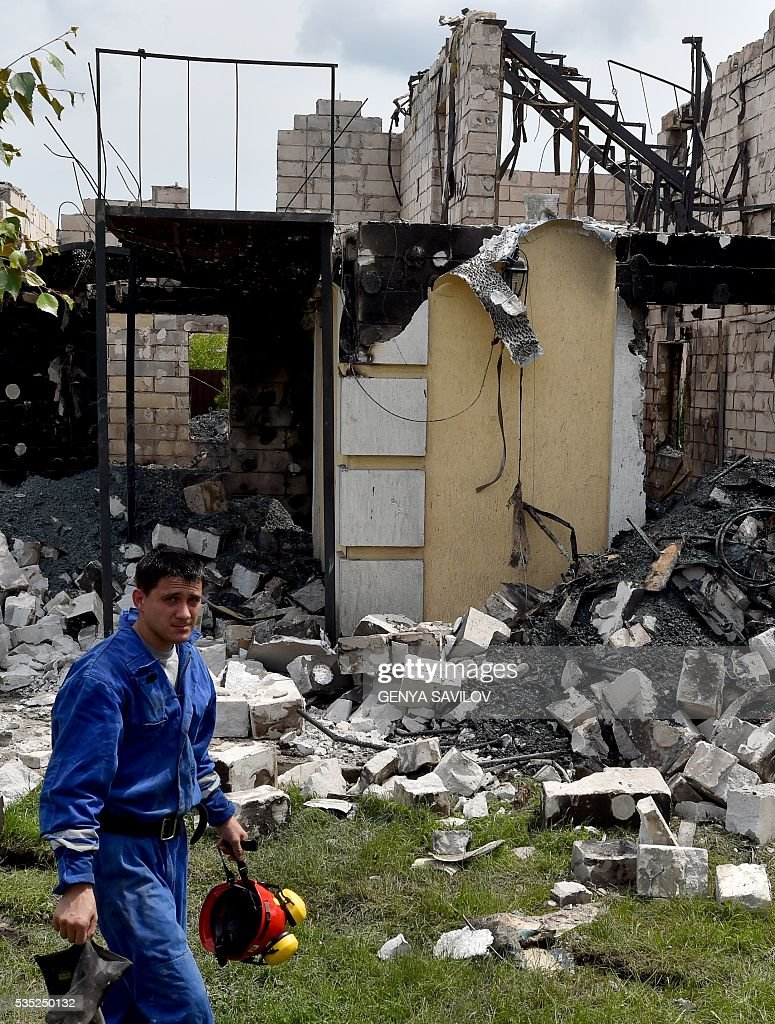 A rescue worker looks on during the investigation of the site of a fire in the village of Litochky, on May 29, 2016. Seventeen people died when a makeshift home for elderly people outside the Ukrainian capital Kiev caught fire in the early hours of May 29, the latest tragedy to shake the conflict-riven country. The fire tore through the two-storey shelter for the elderly which is in the village of Litochky, located some 50 kilometres (31 miles) north of Kiev. / AFP / GENYA