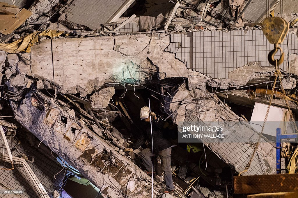 A rescue worker measures gaps in the rubble of a collapsed building in the southern Taiwanese city of Tainan following a strong 6.4-magnitude earthquake that struck early on February 6, 2016. Relatives of residents trapped in a 16-storey apartment complex felled by a powerful earthquake in Taiwan that killed 14 people were praying for miracles Saturday as rescuers sought survivors, with more than 150 missing in the quake zone. / AFP / ANTHONY WALLACE