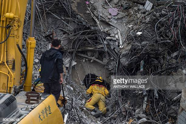 TOPSHOT A rescue worker peers into a gap during the search and rescue operation at the WeiKuan complex which collapsed in the 64 magnitude earthquake...