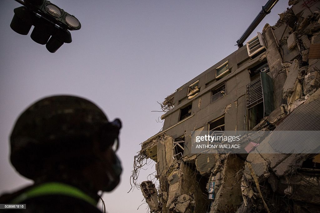 A rescue worker prepares to look for survivors in the remains of a building which collapsed in the 6.4 magnitude earthquake, in the southern Taiwanese city of Tainan on February 8, 2016. Rescuers raced on February 7 to free around 120 people buried under the rubble of an apartment complex felled by an earthquake in southern Taiwan that left 34 confirmed dead, as an investigation began into the collapse. AFP PHOTO / ANTHONY WALLACE / AFP / ANTHONY WALLACE