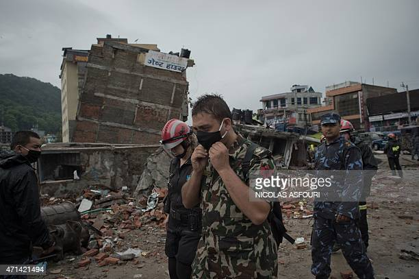 A rescue worker puts on a mask next to earthquake debris in the Nepalese capital Kathmandu on April 28 2015 Hungry and desperate villagers rushed...