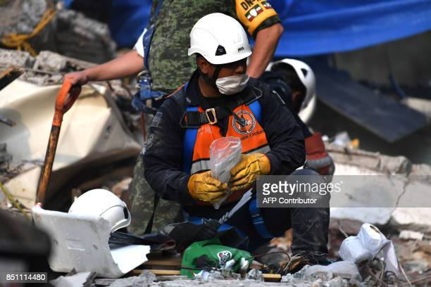 A rescue worker recovers objects and belongings that can help identify victims during the search for survivors and bodies in Mexico City on September...