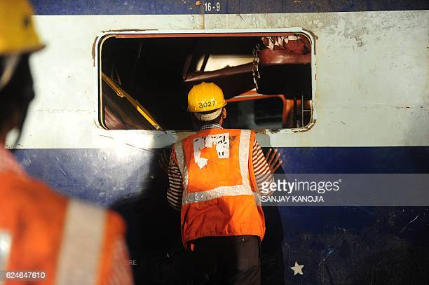 TOPSHOT A rescue worker searches for survivors in the wreckage of a derailed train near Pukhrayan in Kanpur district on November 20 2016 Emergency...