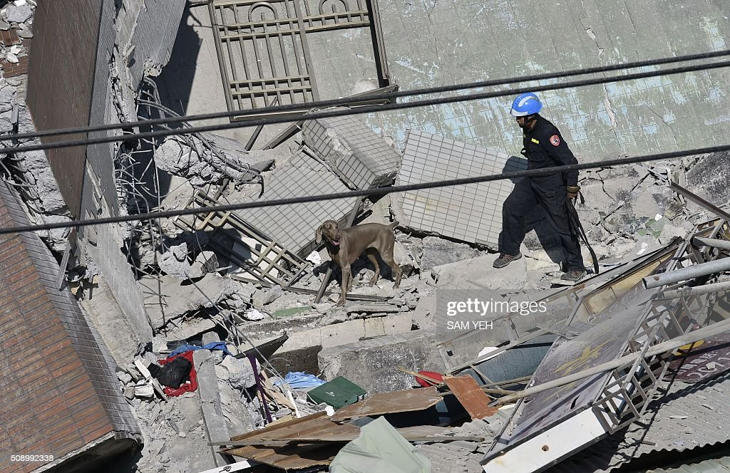 A rescue worker searches the rubble of the Wei-Kuan complex which collapsed in the 6.4 magnitude earthquake, in the southern Taiwanese city of Tainan on February 8, 2016. Two survivors were on February 8 rescued from the rubble of an apartment complex in Taiwan felled by an earthquake, after being trapped for more than 50 hours. AFP PHOTO / Sam Yeh / AFP / SAM YEH