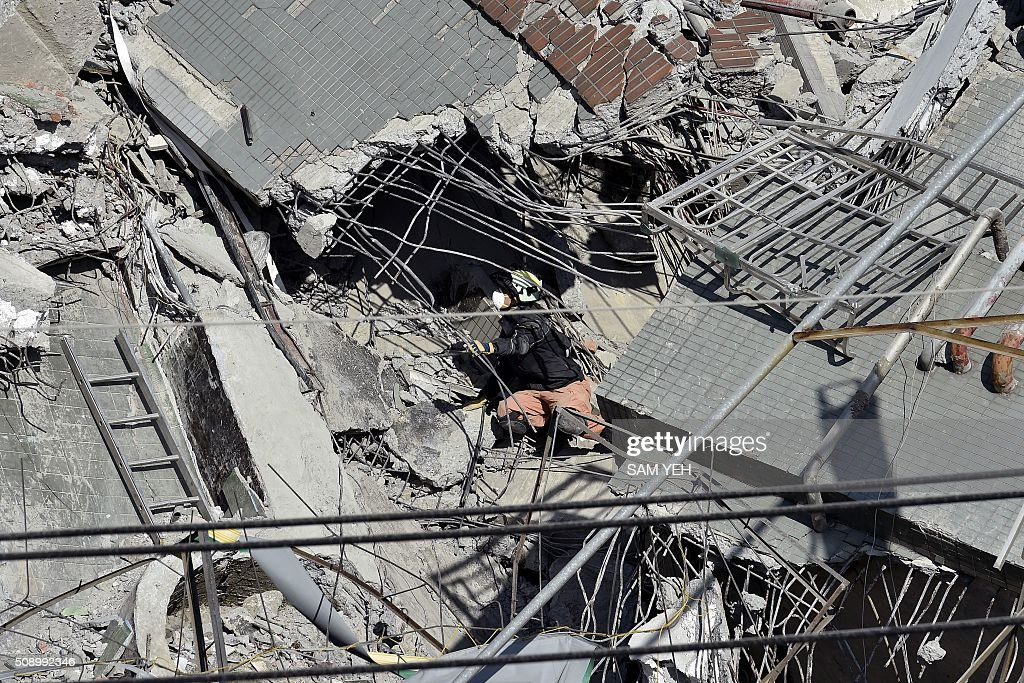 A rescue worker (C) searches the rubble of the Wei-Kuan complex which collapsed in the 6.4 magnitude earthquake, in the southern Taiwanese city of Tainan on February 8, 2016. Two survivors were on February 8 rescued from the rubble of an apartment complex in Taiwan felled by an earthquake, after being trapped for more than 50 hours. AFP PHOTO / Sam Yeh / AFP / SAM YEH