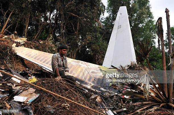 A rescue worker sits at the crash site of an Air India Boeing 737800 aircraft which crashed upon landing in Mangalore on May 22 2010 An Air India...