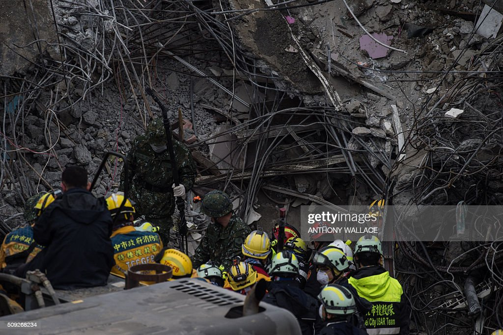 A rescue worker (R) speaks to his colleagues after a probe for finding signs of life was placed into a gap on what was the top of the Wei-Kuan complex which collapsed in the 6.4 magnitude earthquake, in the southern Taiwanese city of Tainan on February 10, 2016. The developer of a Taiwan apartment complex that collapsed during a strong earthquake was arrested, as rescuers reported hearing signs of life in the rubble where some 100 people are still trapped. AFP PHOTO / ANTHONY WALLACE / AFP / ANTHONY WALLACE