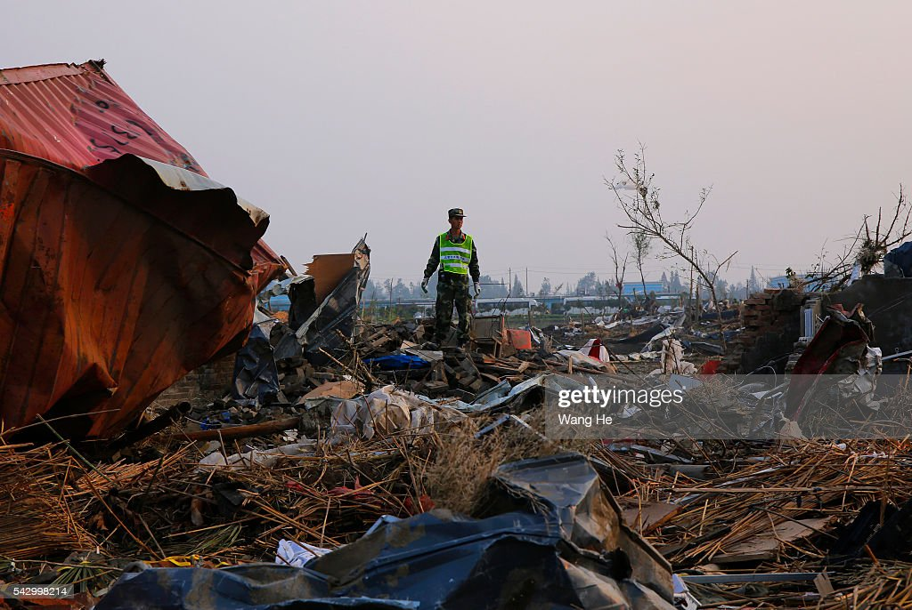 A rescue worker standing in front of a damaged house in Beichen Village of Chenliang Township in Funing, Yancheng, east China's Jiangsu Province on June 25, 2016. A total of 98 people were killed after severe storms in several towns in Jiangsu on Thursday, local rescue headquarters said on Friday. About 846 people sustained injuries, 200 of whom were seriously wounded, it said. More than 8,600 houses, two elementary schools and eight factory buildings were damaged in the counties of Funing and Sheyang, and parts of Yancheng City along the eastern coast of China on June 25, 2016 in Yancheng China.