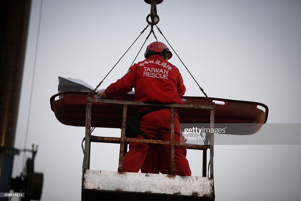 Rescue worker use a crane to transport a victim found in the rubble at the Wei-kuan apartment complex on the second day of rescue operations on February 7, 2016 in Tainan, Taiwan. A magnitude 6.4 earthquake hit southern Taiwan early Saturday, toppling several buildings, killing at least fourteen people, and leaving over one hundred missing in Tainan.