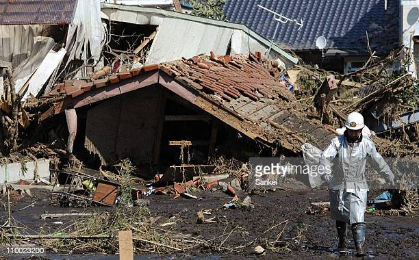 A rescue worker walks around houses ruined by a tsunami after an 89 magnitude earthquake on March 12 2011 in Minamisoma Fukushima Japan An earthquake...