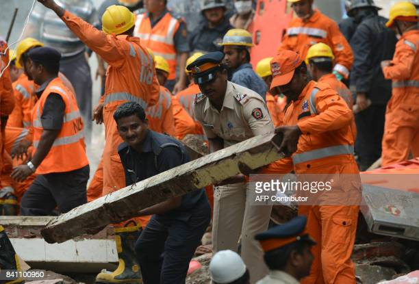 Rescue workers and a policeman help clear debris as they look for survivors at the building collapse site in Mumbai on August 31 2017 At least three...