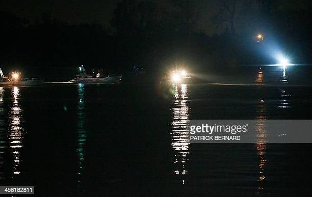 Rescue workers and divers look out from a boat during a rescue operation at the site of a helicopter crash in which a Chinese billionaire his son and...