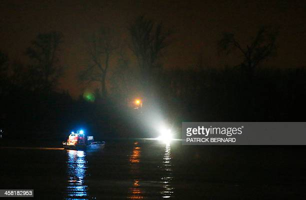Rescue workers and divers look out from boats during a rescue operation at the site of a helicopter crash in which a Chinese billionaire his son and...