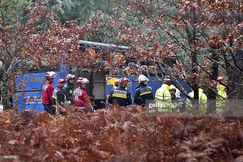 Rescue workers and firefighters stand next to a bus which crashed on the IC8 road near Carvalhal, in the central Castelo Branco district, on January 27, 2013. Ten people were killed and 33 were hurt when a coach slid off a rain-soaked road and plunged into a ravine in central Portugal today, rescue services said. More than 250 firefighters, 88 emergency vehicles and a helicopter were deployed to the scene. The accident occurred around 0845 GMT