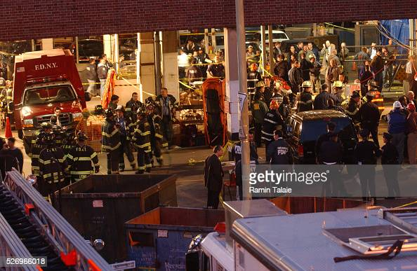 Rescue workers and firemen gather at the scene where a Staten Island Ferry crashed into a pier killing 10 and injuring over 50 passengers