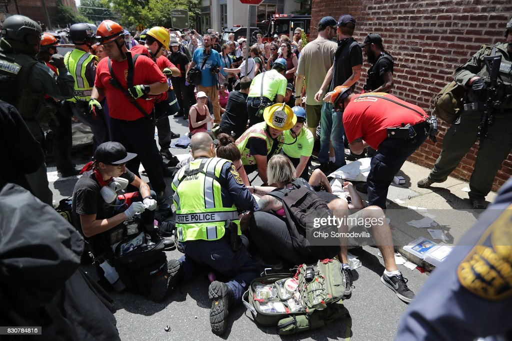 Rescue workers and medics tend to many people who were injured when a car plowed through a crowd of anti-facist counter-demonstrators marching through the downtown shopping district August 12, 2017 in Charlottesville, Virginia. The car plowed through the crowed following the shutdown of the 'Unite the Right' rally by police after white nationalists, neo-Nazis and members of the 'alt-right' and counter-protesters clashed near Emancipation Park, where a statue of Confederate General Robert E. Lee is slated to be removed.