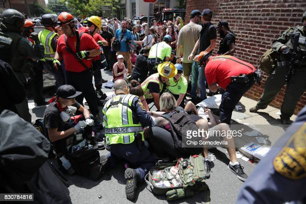 Rescue workers and medics tend to many people who were injured when a car plowed through a crowd of antifacist counterdemonstrators marching through...