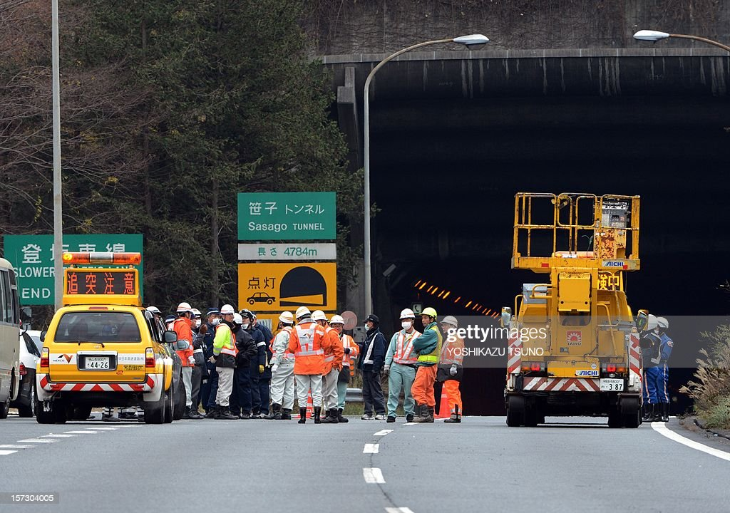 Rescue workers and policeman gather alongside emergency services vehicles on the road leading to the entrance of the collapsed Sasago tunnel on the Chuo expressway in Koshu city, Yamanashi prefecture, some 80-kilometres west of Tokyo on December 2, 2012. At least seven people are missing after concrete ceiling panels along a section of highway tunnel collapsed in Japan on December 2. AFP PHOTO / Yoshikazu TSUNO