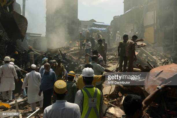 TOPSHOT Rescue workers and residents look for survivors at the site of a building collapse in Mumbai on August 31 2017 At least three people died and...