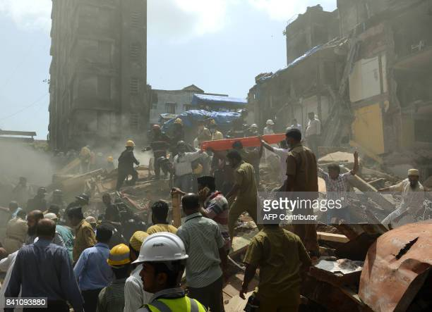 Rescue workers and residents look for survivors at the site of a building collapse in Mumbai on August 31 2017 At least three people died and dozens...