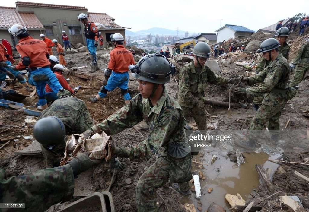 Rescue workers and self defense force soldiers remove debris to search for missing people at the site of a landslide four days after the disaster at a residential area in Hiroshima, western Japan on August 24, 2014. The death toll from devastating midweek landslides in Hiroshima rose to 50 as fresh rain stoked fears of more disasters and hampered the round-the-clock search for survivors.