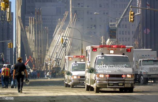 Rescue workers and vehicles move around the wreckage of the World Trade Center September 13 2001 in New York City Rescue efforts continued two days...
