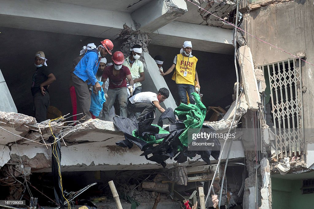 Rescue workers and volunteers remove clothing garments from the building as they search for victims amongst the collapsed Rana Plaza building in Dhaka, Bangladesh, on Friday, April 26, 2013. The day after a Bangladesh building collapsed, killing more than 290 people, disagreement emerged over whether the owner obtained appropriate construction permits, adding to concerns over worker safety in the country's garment industry. Photographer: Jeff Holt/Bloomberg via Getty Images