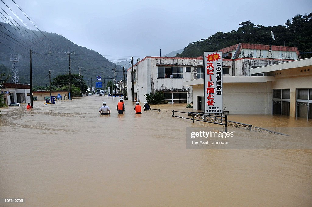 Rescue workers approach in the flooded road to the building where people evacuated in the second floor on October 20, 2010 in Amami, Kagoshima, Japan. Amami Oshima Island recorded 647mm rainfall on October 20.