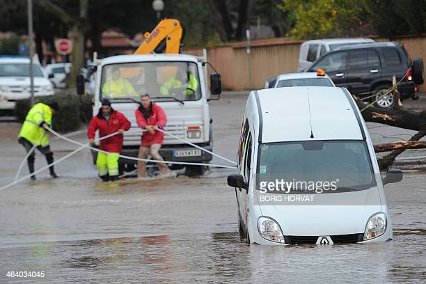 Rescue workers are seen in the harbour of La LondelesMaures southeastern France on Januray 20 2014 River levels were receding early today in...