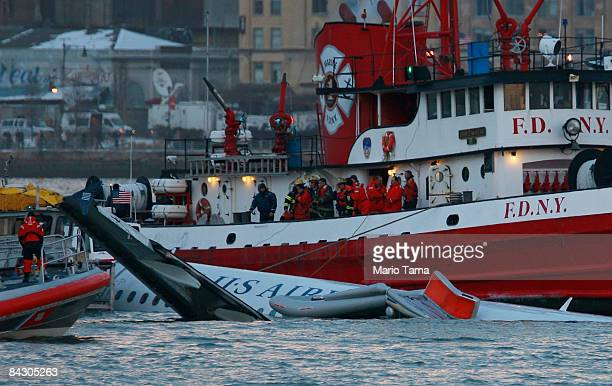 Rescue workers assist a New York City Fire Department boat pulling a US Airways plane floating in the water after crashing into the Hudson River in...