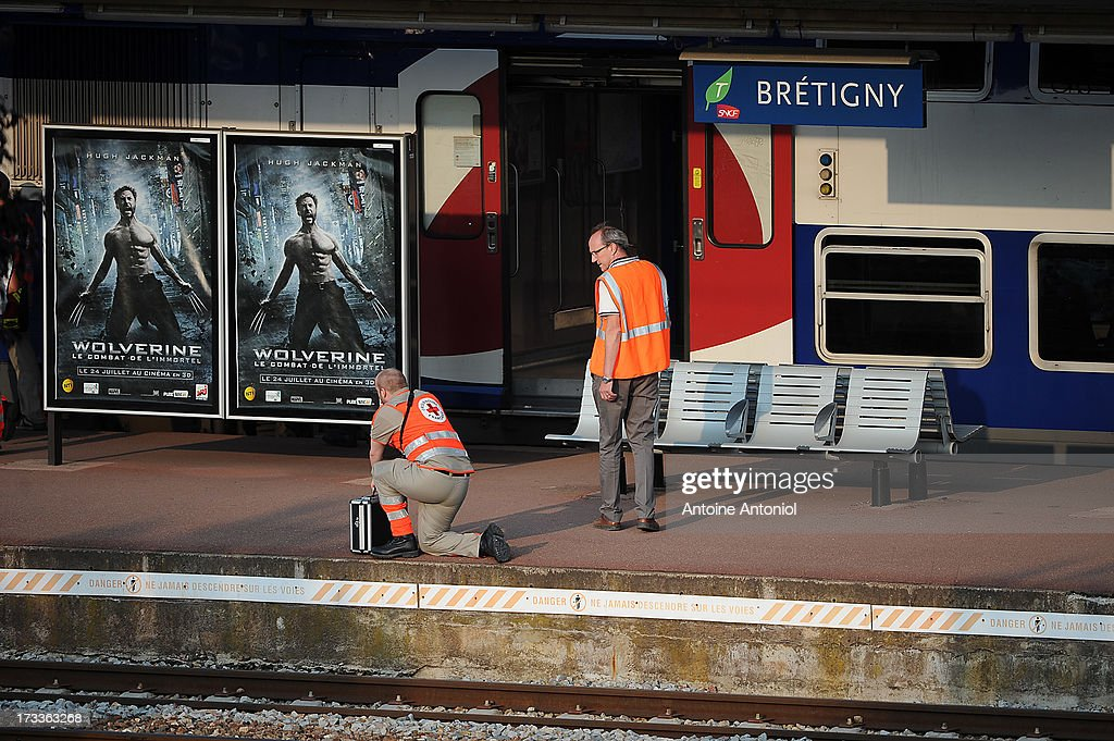 Rescue workers attend the scene after a train accident at the railway station on July 12, 2013 in Bretigny-sur-Orge, France. An intercity train carring 385 passengers, travelling from Paris towards Limoges, derailed crashing into a station platform leaving six people dead and a further 26 injured.