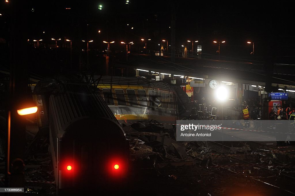 Rescue workers attend the scene alongside derailed carriages after a train accident on July 12, 2013 in Bretigny-sur-Orge, France. An intercity train carrying 385 passengers, traveling from Paris towards Limoges, derailed crashing into a station platform leaving six people dead and a further 26 injured. on July 12, 2013 in Bretigny-sur-Orge, France.