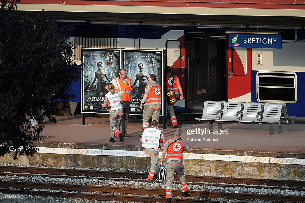 Rescue workers attend the scene at the railway station after a train accident on July 12, 2013 in Bretigny-sur-Orge, France. An intercity train carring 385 passengers, travelling from Paris towards Limoges, derailed crashing into a station platform leaving six people dead and a further 26 injured.