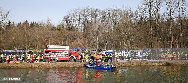 Rescue workers attend the wreckage of two trains that collided headon several hours before in Bavaria on February 9 2016 near Bad Aibling Germany...