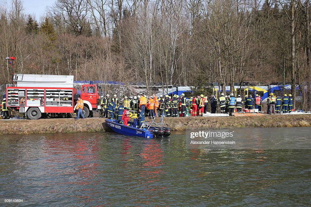 Rescue workers attend the wreckage of two trains that collided headon several hours earlier in Bavaria on February 9 2016 near Bad Aibling Germany...