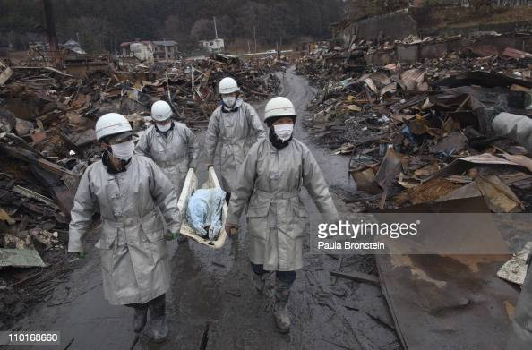 Rescue workers carry a charred body from the rubble of a village destroyed by the devastating earthquake fires and tsunami March 16 2011 in Kesennuma...