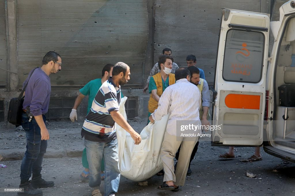 Rescue workers carry a dead body of a civilian after Assad forces hit residential areas with 'naval mines', thrown from helicopters in Kallese District of Aleppo, Syria on May 30, 2016.