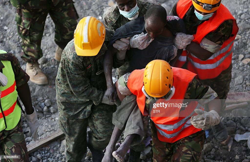 Rescue workers carry a survivor from the rubble of an apartment block on May 5, 2016 in Nairobi, after it collapsed six days ago. Four people were pulled alive May 5 from the rubble of an apartment block that collapsed six days ago when heavy rains hit Nairobi, causing floods and landslides in the Kenyan capital. / AFP / STR
