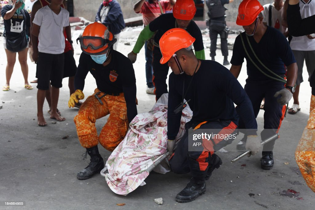 Rescue workers carry a victim's body recovered from rubble in Cebu City, Philippines after a major 7.1 magnitude earthquake struck the region on October 15, 2013. At least 20 people were killed on October 15 when the earthquake tore down buildings across three islands that are among the Philippines' most popular tourist attractions, authorities said. AFP PHOTO / Chester Baldicantos