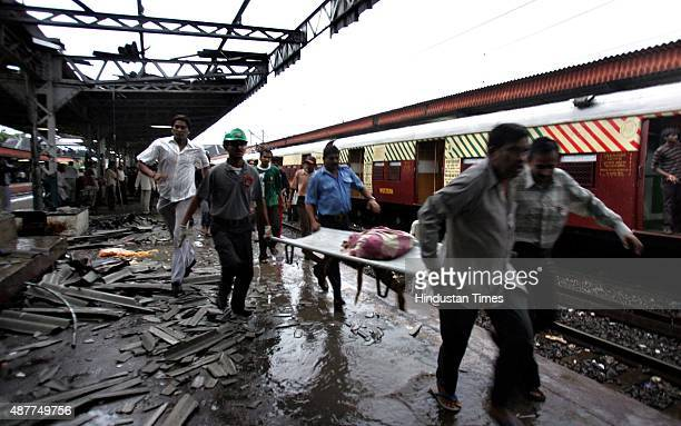 Rescue workers carry an injured passenger to the hospital from inside the mangled compartment of one of the blast affected local trains at Mahim...