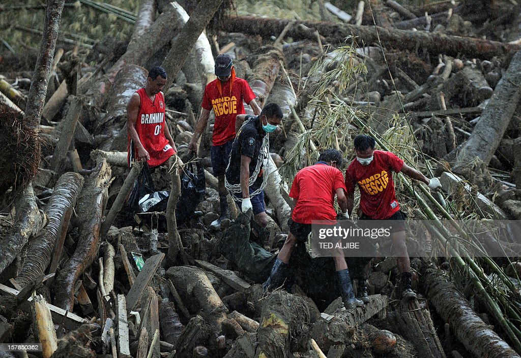 Rescue workers carry dead bodies, victims of flash floods at the height Typhoon Bopha and retrieved from amongst the debris of logs in New Bataan, Compostela Valley province on December 7, 2012. President Benigno Aquino vowed action on the Philippines' typhoon disasters December 7 as bruised and grieving survivors tried to recover from the latest that left nearly 500 people dead