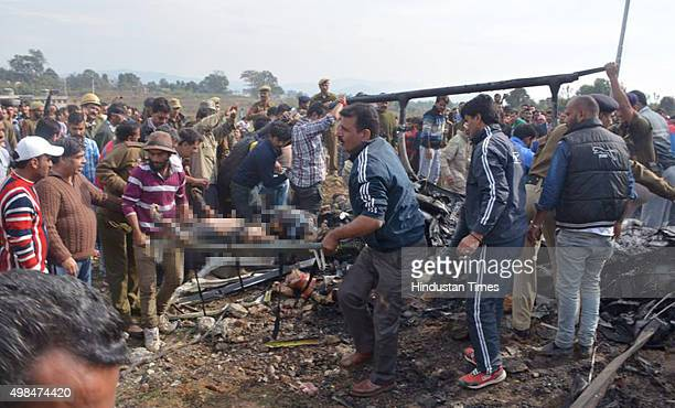 Rescue workers carry the body of a man who was killed in a helicopter crash at Katra on November 23 2015 in Jammu India Seven Vaishno Devibound...