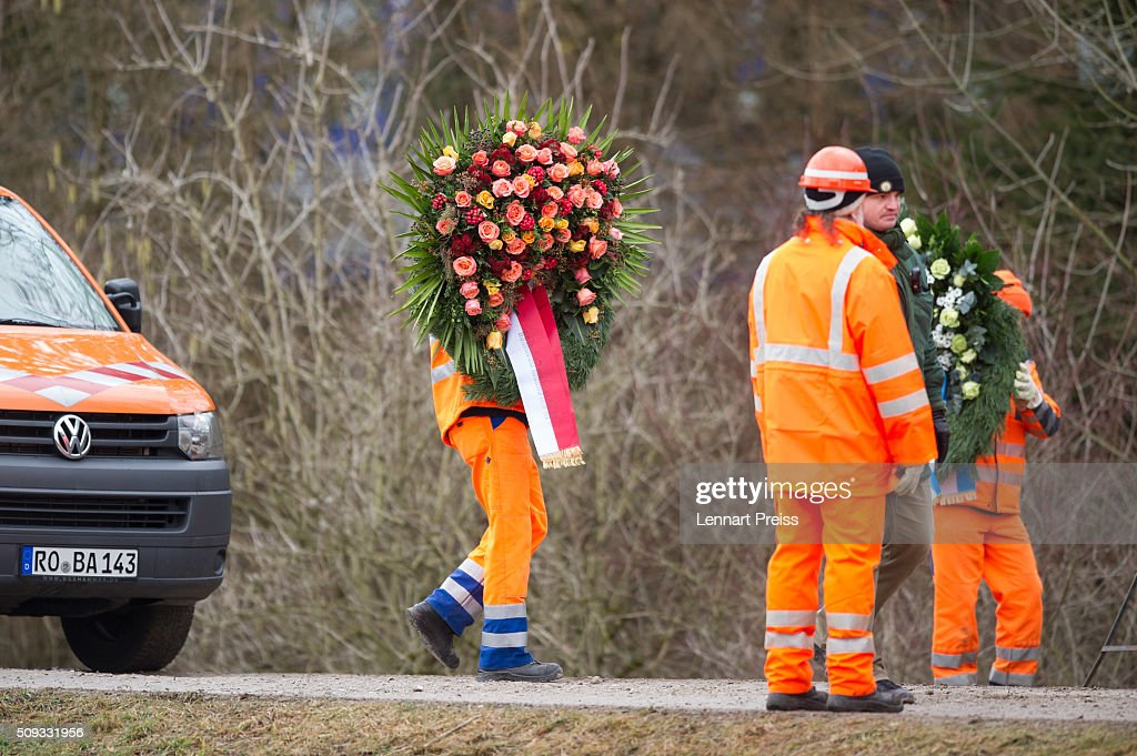 Rescue workers carry two chaplets near the wreckage of two trains that collided head-on the day before in Bavaria on February 10, 2016 near Bad Aibling, Germany. Authorities say at least nine people are dead and over 100 injured in the collision between two trains of the Meridian local commuter train service that occurred at approximately 7:00 am yesterday.